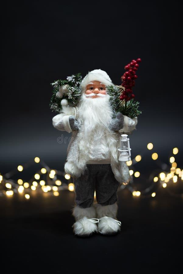 Magisk glad Santa Claus leksakstående som skjutas mot magiska guld- ljus arkivbilder