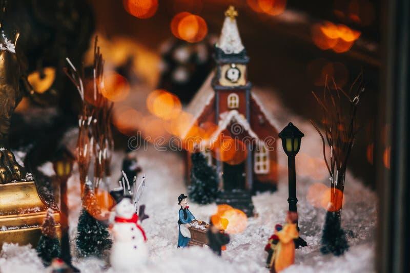 Magisk liten julstad i miniatyr med snö, snögubbe, ligh royaltyfria bilder