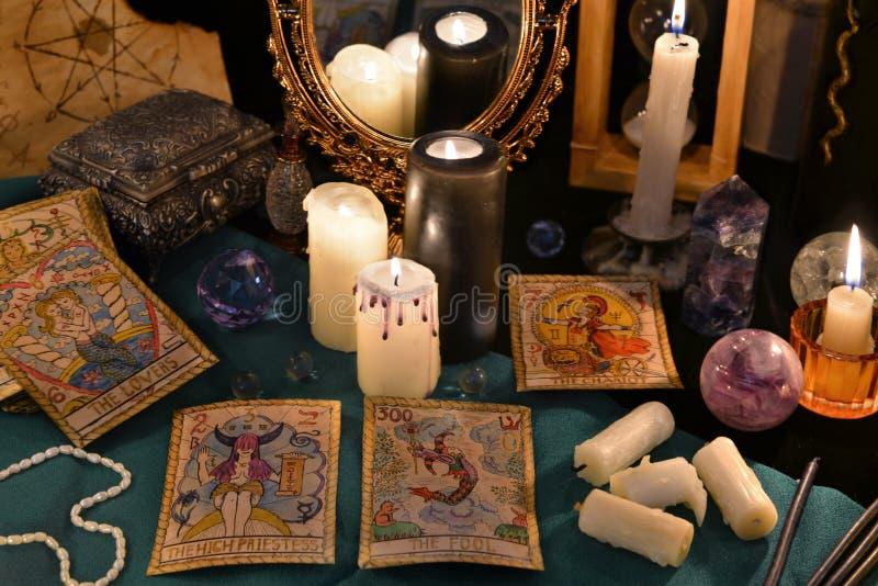 Magisk stilleben med kristaller, tarokkorten och stearinljus vid mirrowen fotografering för bildbyråer