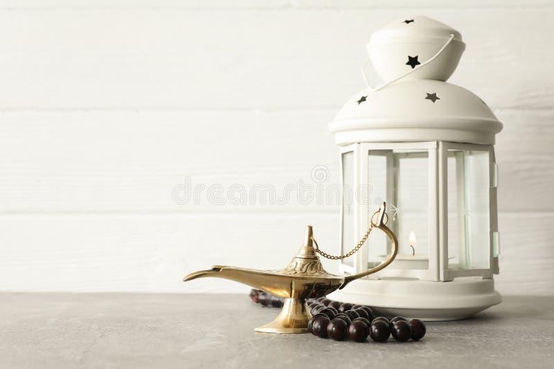 Magiska Aladdin Lamp med bönpärlor och Ramadanlykta på den gråa tabellen royaltyfria bilder
