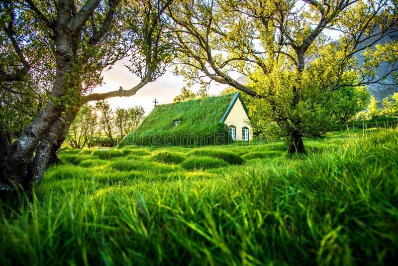 Magiskt charmigt härligt landskap med torvatakkyrkan i gammal Island traditionell stil och den mystiska kyrkogården i Hof, royaltyfri bild