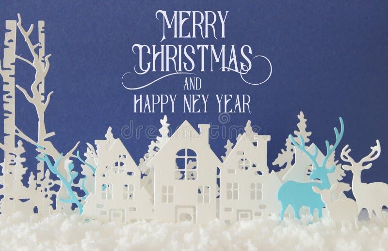 Magiskt landskap för bakgrund för vinter för julpapperssnitt med hus, träd, hjortar och den insnöade framdelen av blå bakgrund stock illustrationer