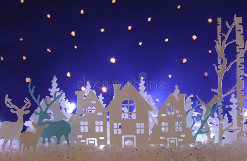 Magiskt landskap för bakgrund för vinter för julpapperssnitt med hus, träd, hjortar och den insnöade framdelen av stjärnklar himm vektor illustrationer