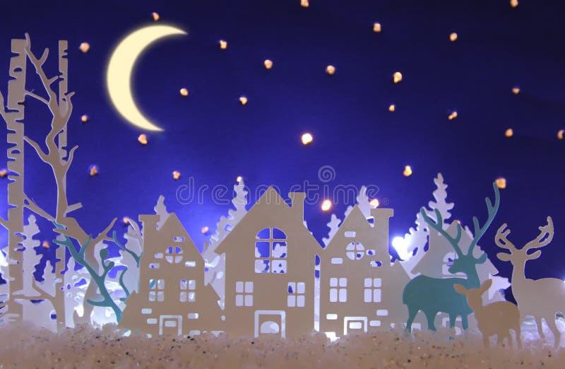 Magiskt landskap för bakgrund för vinter för julpapperssnitt med hus, träd, hjortar och den insnöade framdelen av stjärnklar himm royaltyfri foto