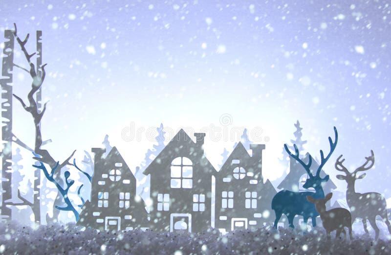 Magiskt landskap för bakgrund för vinter för julpapperssnitt med hus, träd, hjortar och den insnöade framdelen av bakgrund för vi arkivfoton