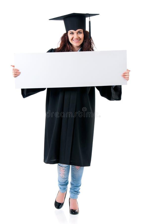 Magisterski dziewczyna uczeń w salopie pokazuje puste miejsce fotografia stock