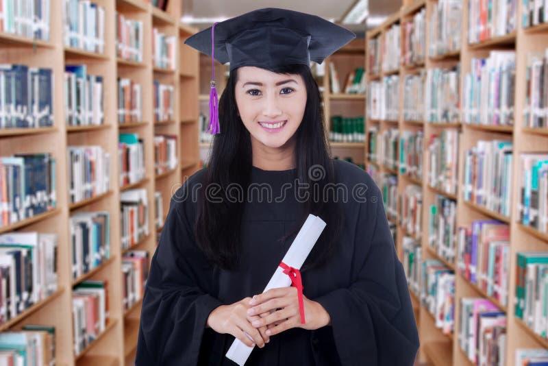 Magistrant/magistrantka mienie dyplom w bibliotece obrazy royalty free