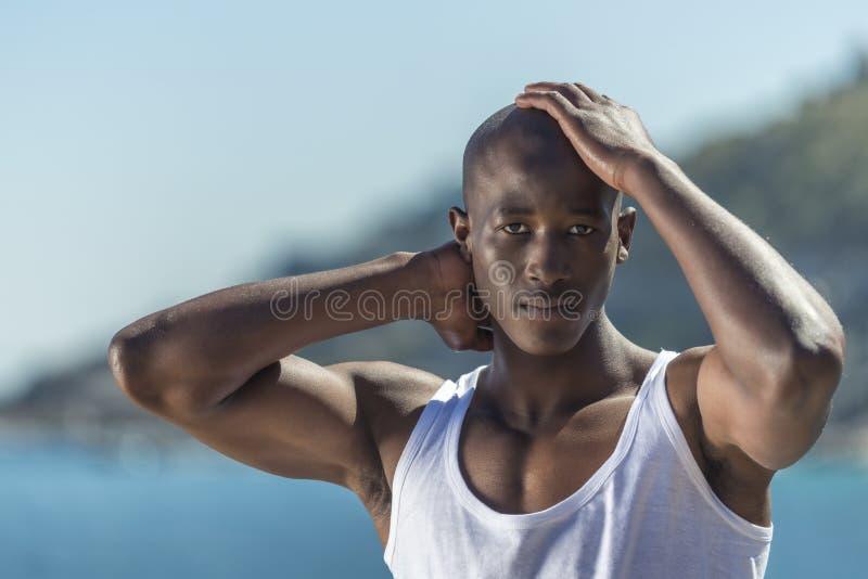 Maglia bianca d'uso dell'uomo di colore africano e brevi jeans blu fotografie stock libere da diritti