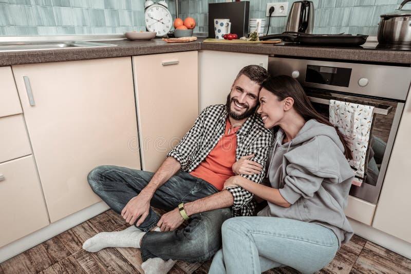 Maglia con cappuccio d'uso della giovane moglie mora che abbraccia il suo marito fotografia stock libera da diritti