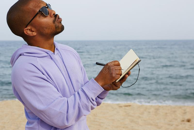 Maglia con cappuccio d'uso ed occhiali da sole dei pantaloni a vita bassa afroamericani sicuri pensierosi del tipo che fanno le n immagini stock libere da diritti