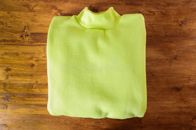 Maglia con cappuccio verde su fondo di legno fotografie stock