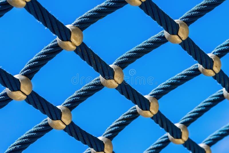 Maglia della corda contro un primo piano luminoso del cielo blu, un parco rampicante, un campo da giuoco per gioco e uno sport immagine stock