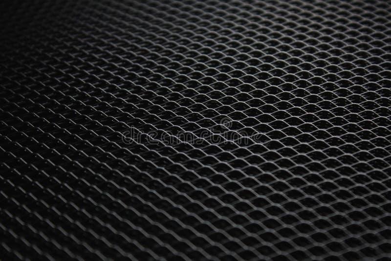 Maglia metallica nera nell'ambito della sorgente luminosa tenue fotografie stock