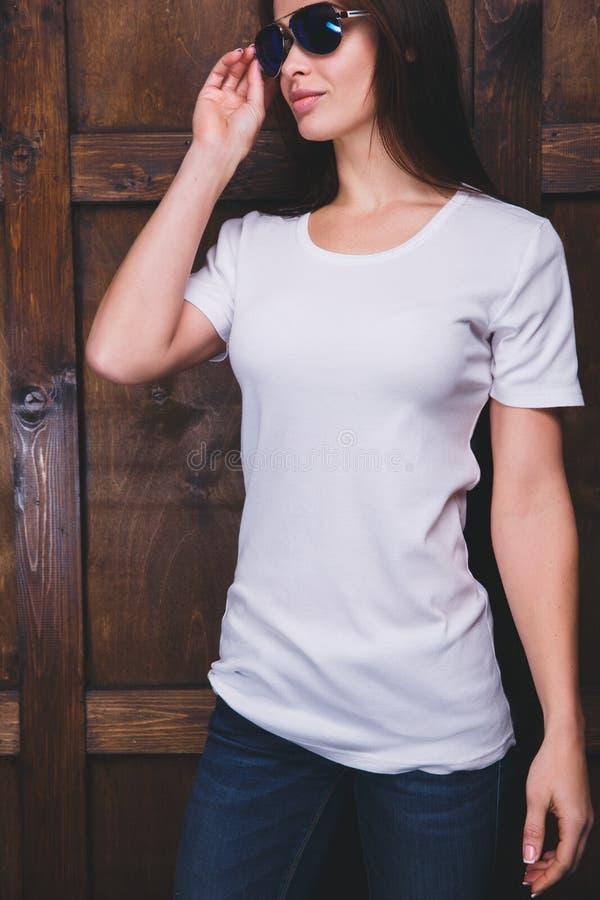 Maglietta bianca d'uso della donna davanti alla parete di legno fotografie stock