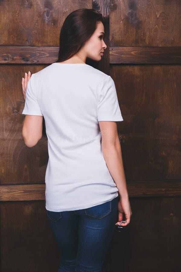 Maglietta bianca d'uso della donna davanti alla parete di legno, vista posteriore immagini stock libere da diritti