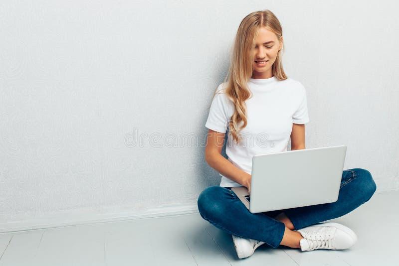 Maglietta bianca d'uso della donna felice che si siede sul pavimento con il computer portatile su fondo grigio fotografia stock