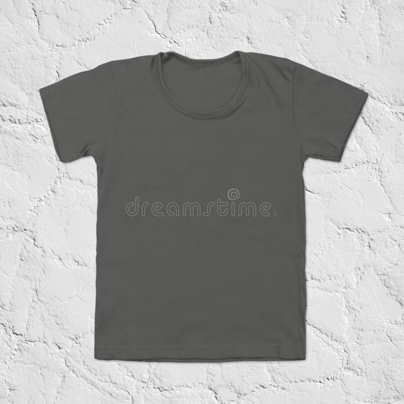 Maglietta in bianco grigia su fondo di pietra scuro fotografie stock