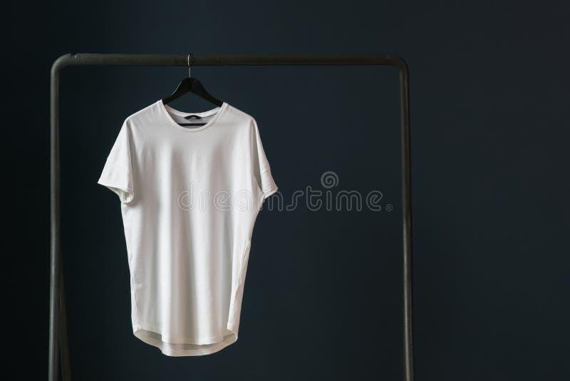 Maglietta con le brevi maniche su un gancio contro lo sfondo di una parete scura fotografia stock libera da diritti