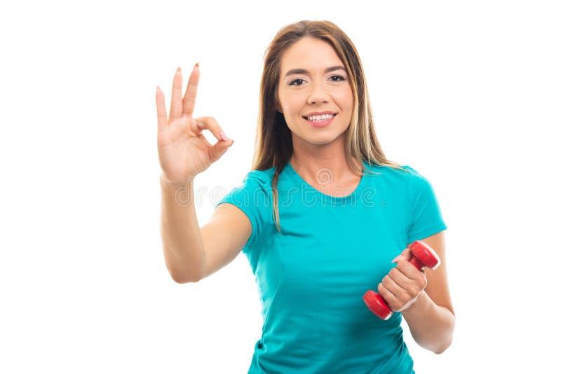 Maglietta d'uso della giovane ragazza graziosa che mostra gesto giusto immagini stock libere da diritti
