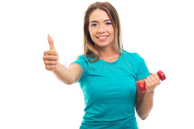 Maglietta d'uso della giovane ragazza graziosa che mostra pollice sul gesto fotografie stock libere da diritti