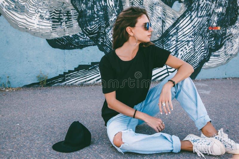 Maglietta di modello ed occhiali da sole normali d'uso che posano sopra la via wal fotografia stock libera da diritti