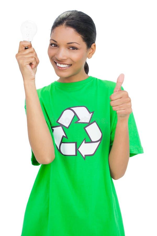 Maglietta di riciclaggio d'uso di modello sorridente che tiene lampadina fotografia stock