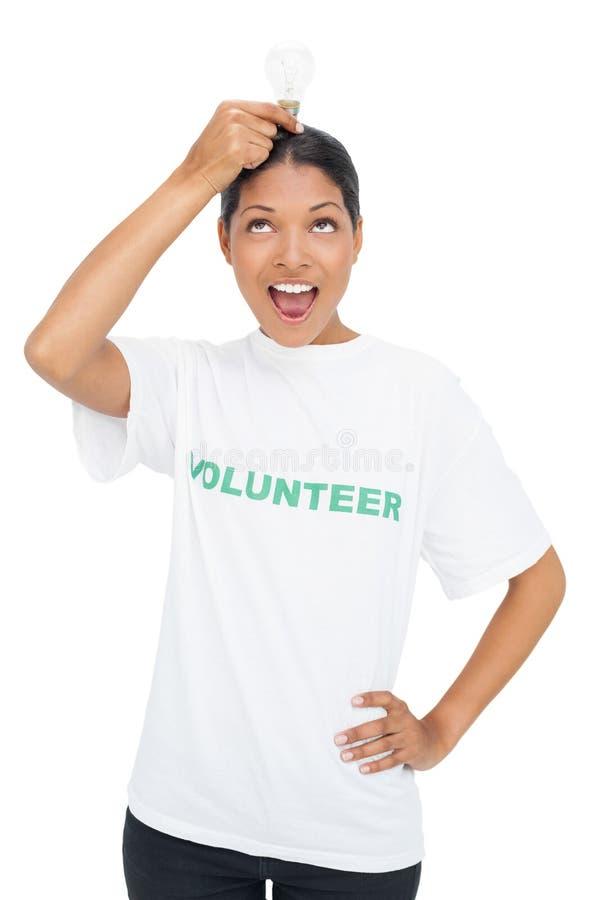 Maglietta volontaria d'uso del modello felice che tiene lampadina sopra la sua testa fotografie stock