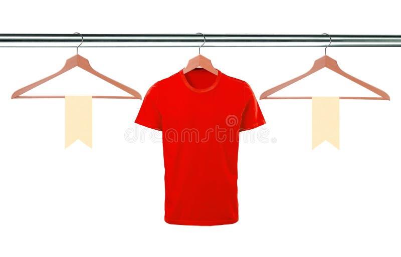 Magliette rosse sui ganci e sulle etichette in bianco isolati sul backgro bianco fotografia stock libera da diritti