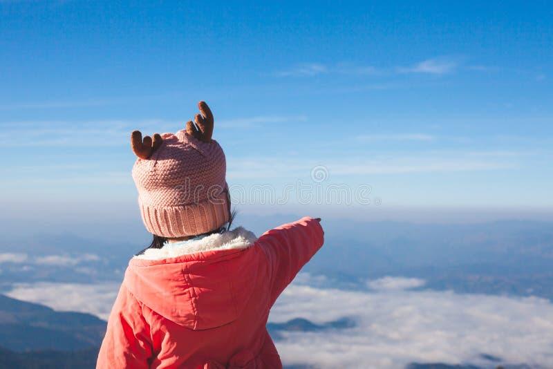 Maglione d'uso della ragazza asiatica sveglia del bambino e cappello caldo sollevare il suo braccio ed indicare la bella natura n fotografia stock libera da diritti
