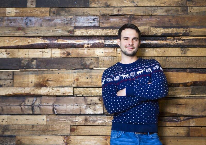 Maglione d'uso di Natale dell'uomo felice contro il fondo della parete fotografie stock libere da diritti