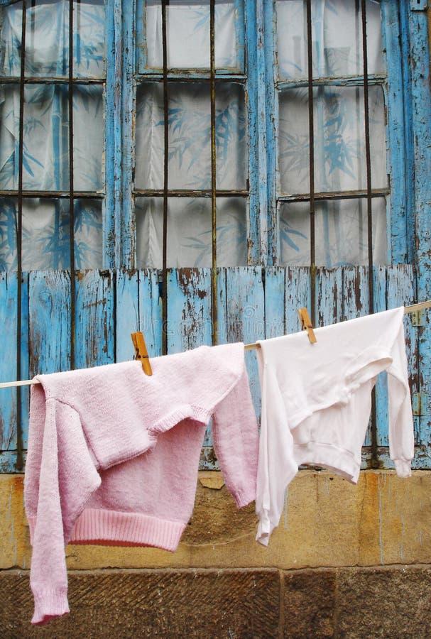 Maglione e maglietta che appendono su una riga di vestiti fotografie stock libere da diritti