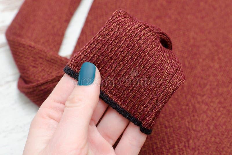 Maglione marrone della manica in una mano femminile concetto alla moda clos fotografia stock libera da diritti