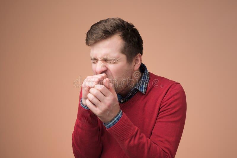 Maglione rosso del manin maturo bello che tossisce molto fotografia stock libera da diritti