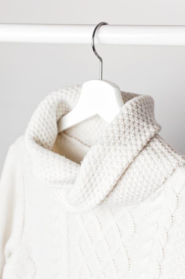 Maglione tricottato bianco della lana su un gancio di legno bianco contro lo sfondo della parete leggera Vestiti di inverno e di  fotografia stock