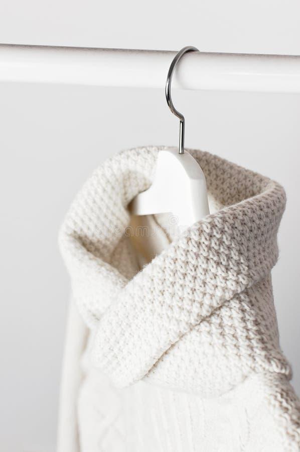 Maglione tricottato bianco della lana su un gancio di legno bianco contro lo sfondo della parete leggera Vestiti di inverno e di  immagini stock libere da diritti