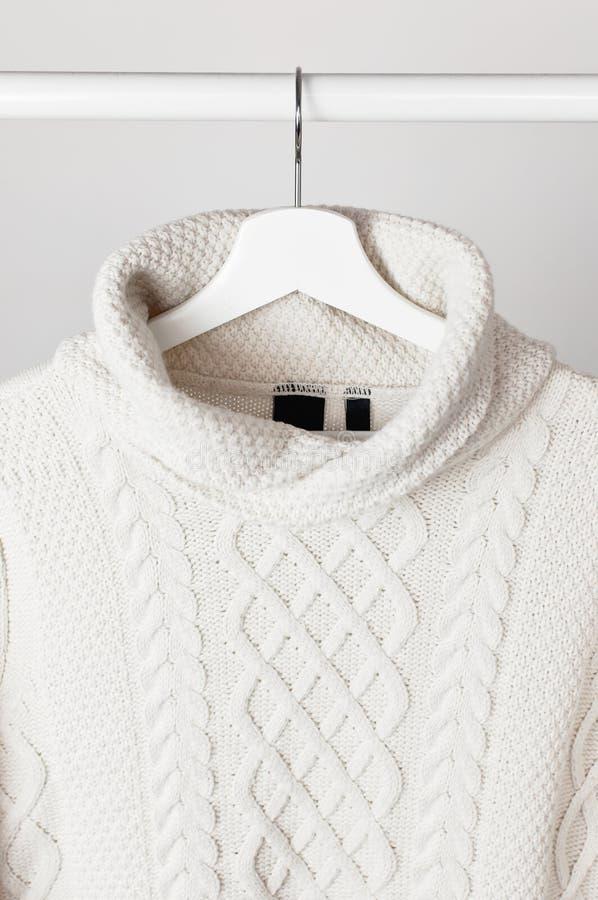 Maglione tricottato bianco della lana su un gancio di legno bianco contro lo sfondo della parete leggera Vestiti di inverno e di  immagine stock libera da diritti