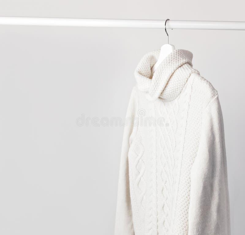 Maglione tricottato bianco della lana su un gancio di legno bianco contro lo sfondo della parete leggera Vestiti di inverno e di  immagini stock