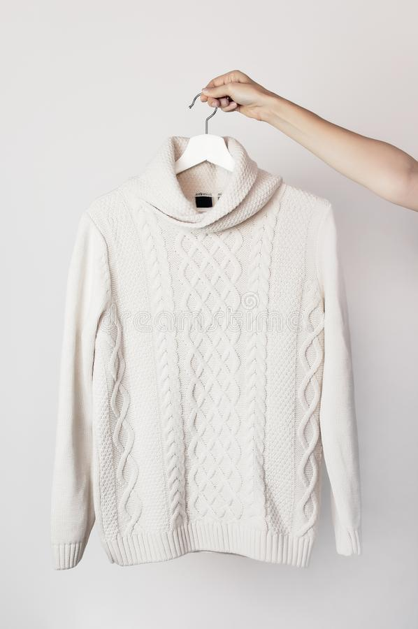 Maglione tricottato bianco della lana su un gancio di legno bianco in mani femminili contro lo sfondo della parete leggera Cl di  immagine stock