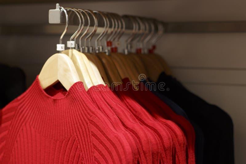 Maglioni tricottati di lana rossi che appendono sui ganci nel deposito, primo piano fotografie stock