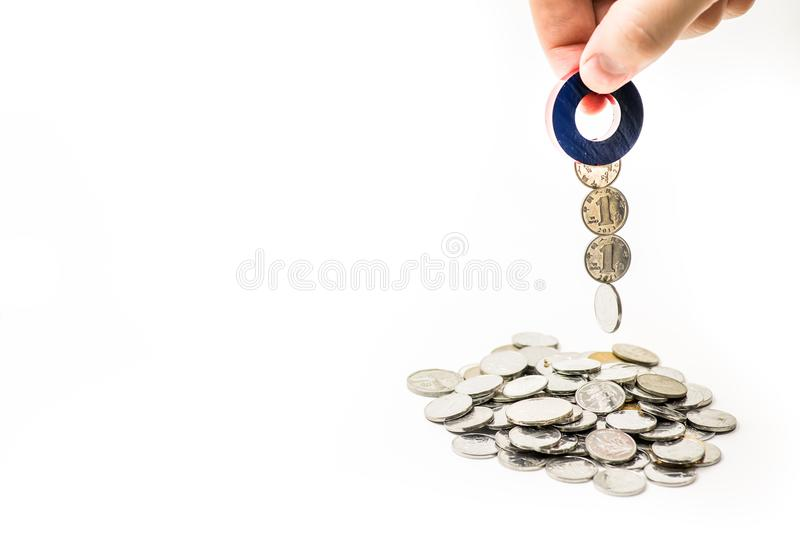 Magneet in een mannelijke hand die van ` s geld van de muntstukstapel aantrekken op witte achtergrond royalty-vrije stock foto