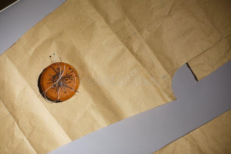 Magnes z wiązką igły kłama na wzorach odziewa target2096_0_ odziewa target2096_0_ Krawiecki przemysł zdjęcie royalty free