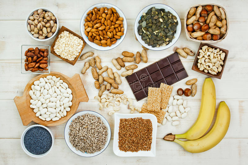 Magnesium in food. Collection products containing magnesium as pumpkin seeds, poppy seed, cashew nuts, beans, raw cocoa beans, almonds, sunflower seeds, oatmeal royalty free stock images