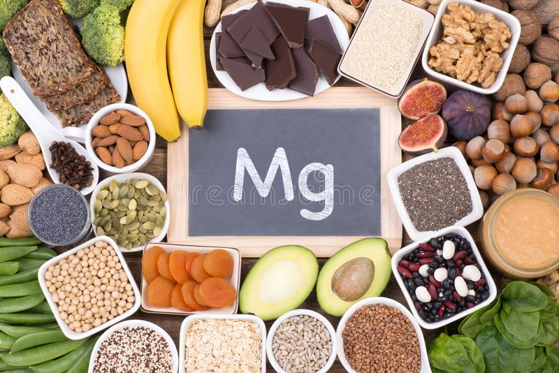 Magnesium food sources, top view on wooden background. Various magnesium food sources such as grains, fruit, vegetables and chocolate, top view on wooden royalty free stock images