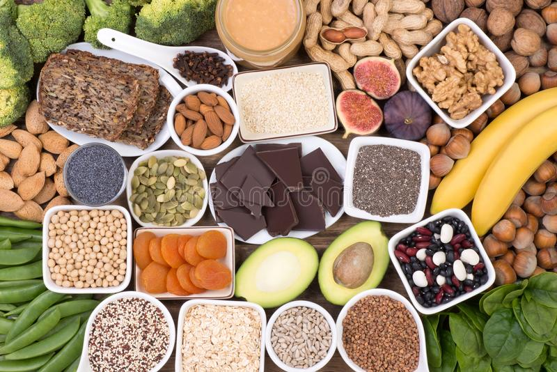 Magnesium food sources, top view on wooden background. Various magnesium food sources such as grains, fruit, vegetables and chocolate, top view on wooden royalty free stock photos