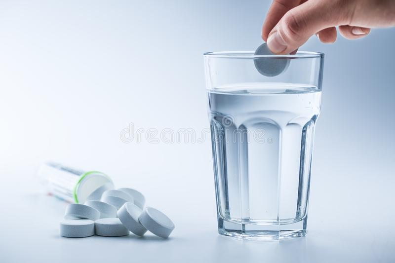 Magnesium pills and cup of clear water on blue white background.  stock image