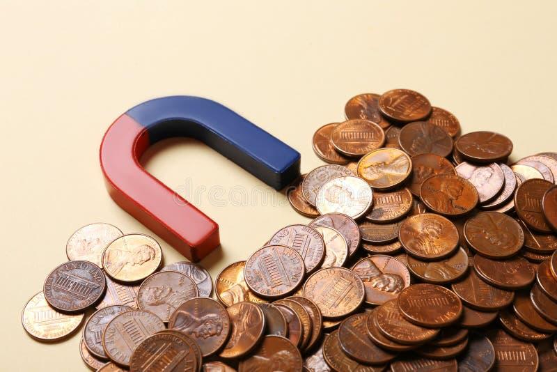 Magnet mit Münzen auf beigem Hintergrund lizenzfreie stockfotografie