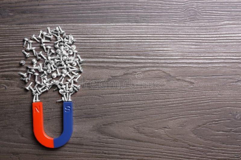 Magnet mit Schrauben auf grauem Holzboden, flache Lage Textbereich lizenzfreie stockbilder