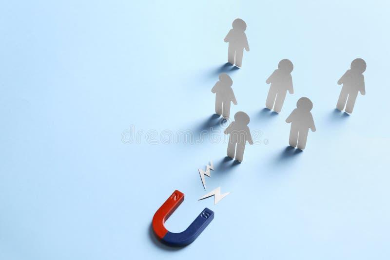 Magnet zieht Papiermenschen auf hellblauem Hintergrund an Unternehmenskonkurrenzkonzept stockfotos