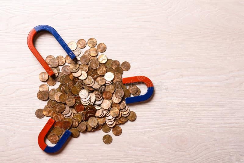 Magnete, die Münzen auf hellen Holzgrundstücken anziehen Textbereich stockfotos