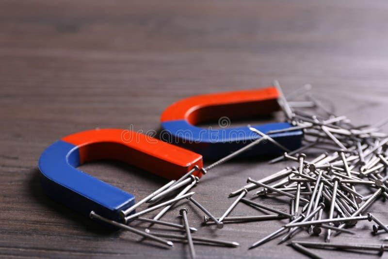 Magnete, die Nägel auf grauem Holzboden anziehen, schließen lizenzfreies stockbild